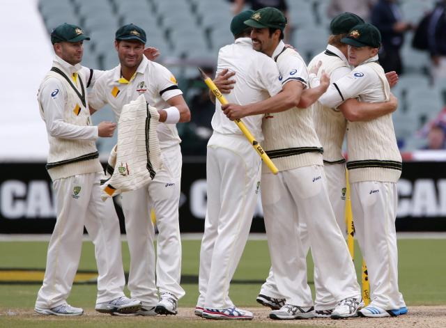 Australia's captain Michael Clarke (L) and Ryan Harris (2nd L) celebrate with team mates after winning the second Ashes cricket test against England at the Adelaide Oval December 9, 2013. Australia captured England's four remaining wickets before lunch to close out an emphatic 218-run victory in the second Ashes test on Monday. REUTERS/David Gray (AUSTRALIA - Tags: SPORT CRICKET)