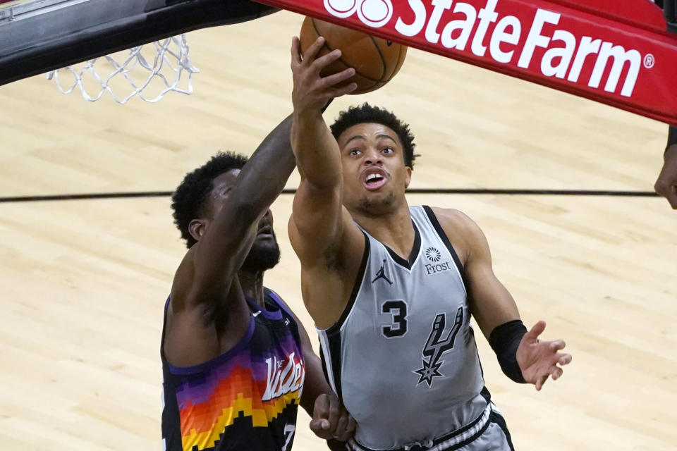 San Antonio Spurs forward Keldon Johnson (3) drives past Phoenix Suns center Deandre Ayton during the first half of an NBA basketball game Saturday, April 17, 2021, in Phoenix. (AP Photo/Rick Scuteri)