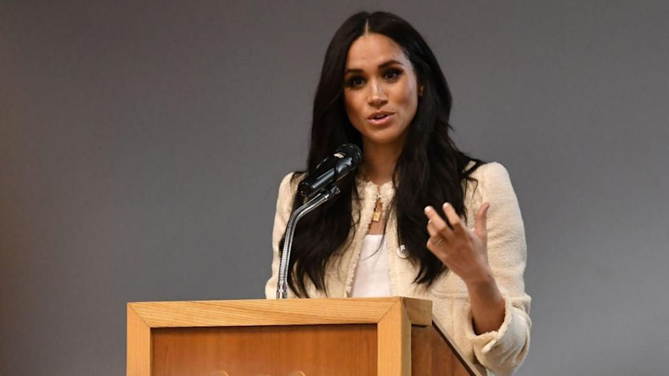 Meghan Markle speaks from behind a podium.