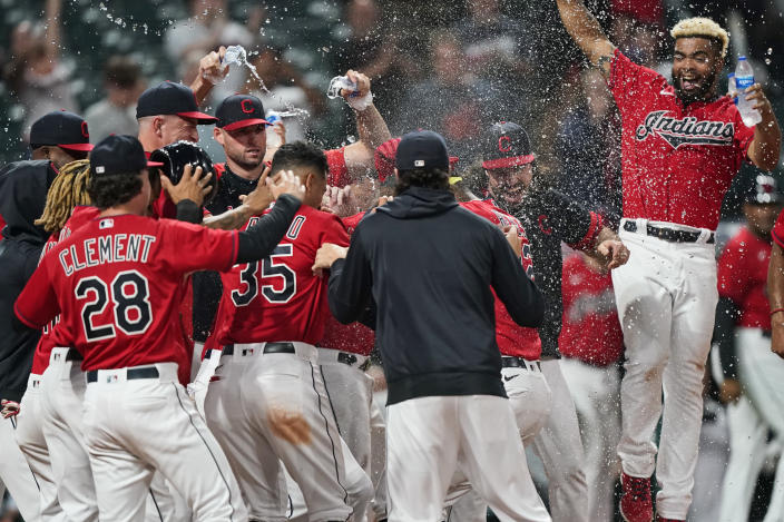 The Cleveland Indians mob Franmil Reyes after Reyes hit a three-run home run in the ninth inning of the team's baseball game against the Kansas City Royals, Thursday, July 8, 2021, in Cleveland. The Indians won 7-4. (AP Photo/Tony Dejak)