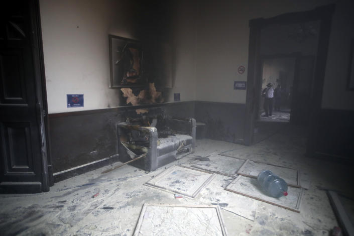 A couch and art work destroyed by fire are seen inside the Congress building after protesters set a part of the building on fire, in Guatemala City, Saturday, Nov. 21, 2020. Hundreds of protesters were protesting in various parts of the country Saturday against Guatemalan President Alejandro Giammattei and members of Congress for the approval of the 2021 budget that reduced funds for education, health and the fight for human rights. (AP Photo/Moises Castillo)