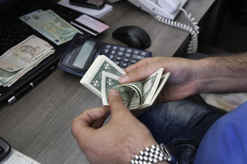 In this photo taken on Wednesday, Oct. 24, 2012, a currency exchange bureau worker counts U.S. dollars in downtown Tehran, Iran. Iranian authorities have been forced to quell protests in recent weeks over the plummeting value of the country's currency which lost nearly 40 percent of its value against the U.S. dollar in a week in early October. With the U.S. election less than 10 days away, both President Obama and Republican challenger Mitt Romney are cautious about discussing potential compromises as Iran's economy shows signs of increasing strain from economic sanctions that seek nuclear concessions. (AP Photo/Vahid Salemi)