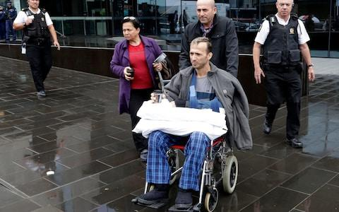 A man in a wheelchair is escorted from outside the High Court in Christchurch - Credit: AP
