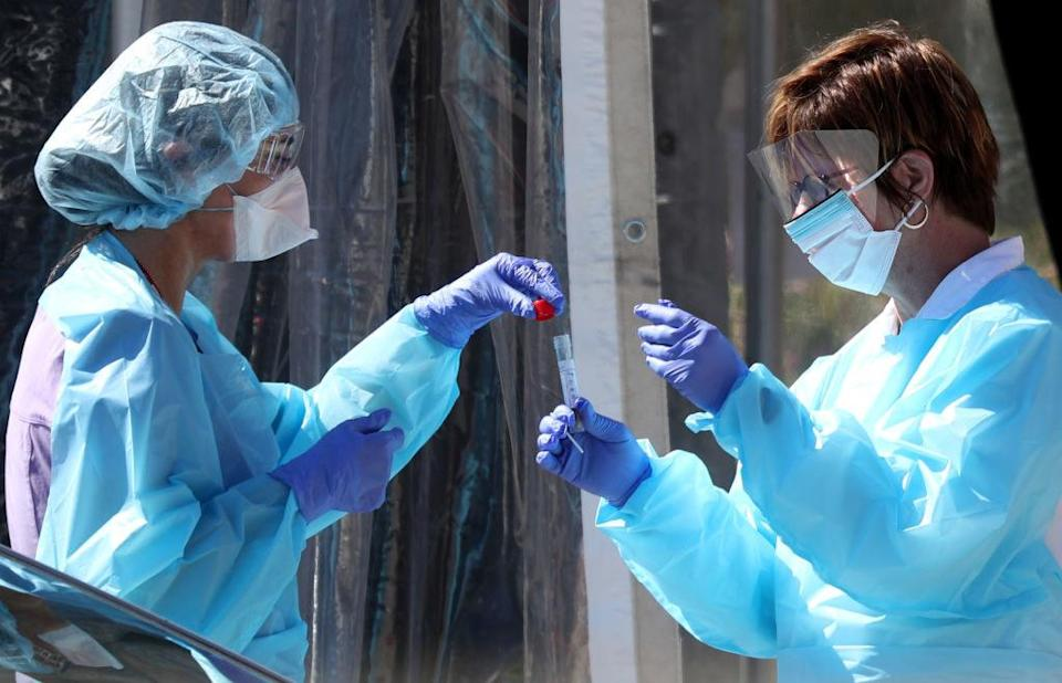 Two medical officials handling a sample
