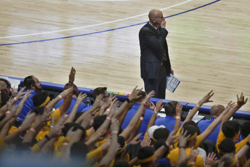 Louisville coach Chris Mack, top watches while the fans in the Pittsburgh student section hold up their hands while Pittsburgh's Justin Champagnie shoots one of the foul shots resulting from the technical foul called on Mack during the second half of an NCAA college basketball game, Tuesday, Jan. 14, 2020, in Pittsburgh. (AP Photo/Keith Srakocic)