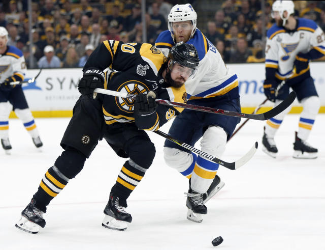 Boston Bruins' Marcus Johansson, left and St. Louis Blues' Carl Gunnarsson, both of Sweden, chase the puck during the second period in Game 5 of the NHL hockey Stanley Cup Final, Thursday, June 6, 2019, in Boston. (AP Photo/Michael Dwyer)