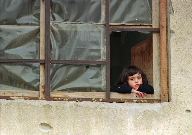 <p>A young girl peers out of a window covered in plastic in place of destroyed glass panes, in Gorazde, Bosnia, Jan. 19, 1996. Encircled by Bosnian Serb forces at the beginning of the war, Gorazde held on as the other eastern Bosnian Muslim enclaves fell. (Photo: Jacqueline Larma/AP) </p>