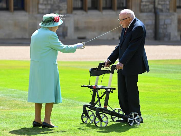 The Queen knights Tom Moore at Windsor Castle in July last yearRex
