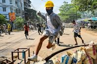 A protester jumps over a makeshift barricade as security forces crack down on a demonstration in Yangon's Thaketa township on March 19, 2021
