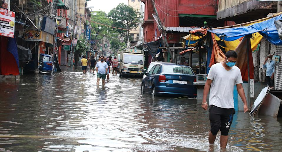 People wade through a flooded street after cyclone Amphan hit Kolkata, India. Source: AAP