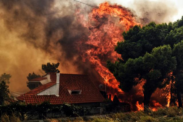 <p>A house is threatened by a huge blaze during a wildfire in Kineta, near Athens, on July 23, 2018. (Photo: Valerie Gache/AFP/Getty Images) </p>