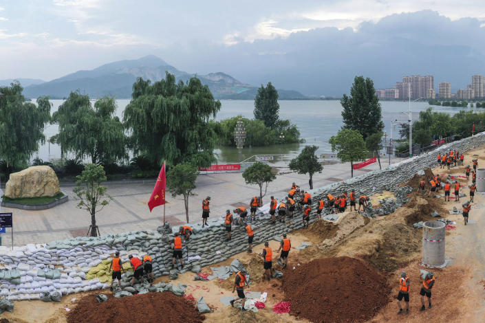 Chinese soldiers build a temporary embankment to contain Poyang Lake which has reached a record level threatening to flood Lushan city in central China's Jiangxi province Monday, July 13, 2020. Chinese authorities forecasted heavy rain across a wide swath of the country prompting evacuation of residents and raising emergency alerts levels. (Chinatopix via AP)