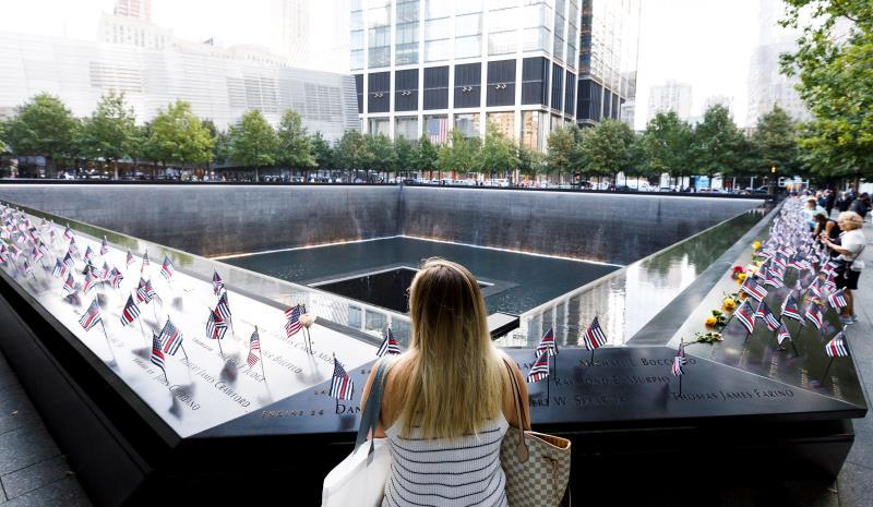 A woman looks out at the North Pool of the National September 11 Memorial during ceremonies marking the 18th anniversary of the September 11, 2001 terrorist attacks in New York, New York, USA, 11 September 2019. EFE/EPA/JUSTIN LANE
