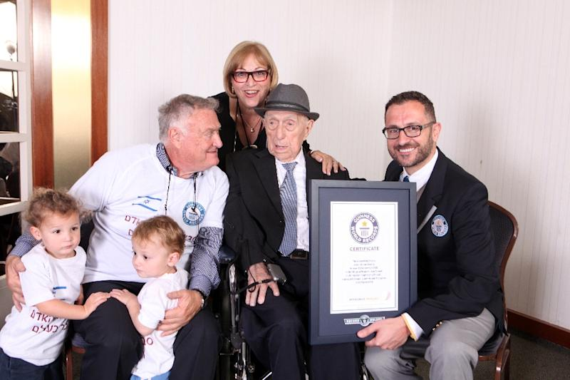 A file picture released by Guinness World Records on March 11, 2016 shows Marco Frigatti (R), head of Records for Guinness World Records, presenting Yisrael Kristal with his certificate of achievement for oldest living man, in the presence of Kristal's daughter, son and two grandchildren