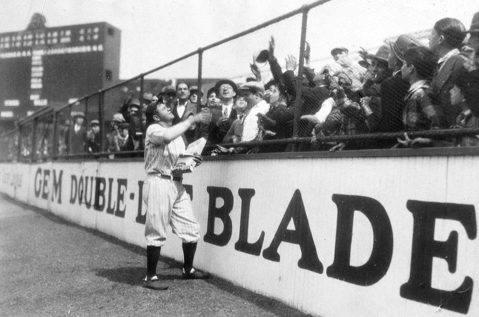 <p>Baseball star Babe Ruth hands out his newly minted candy bars to eager bystanders at Yankee Stadium shortly before the game. </p>