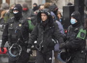 Police detain a person during a demonstration in Montreal, Sunday, Dec. 20, 2020, where people protested measures implemented by the Quebec government to help stop the spread of COVID-19. The COVID-19 pandemic continues in Canada and around the world. (Graham Hughes/The Canadian Press via AP)