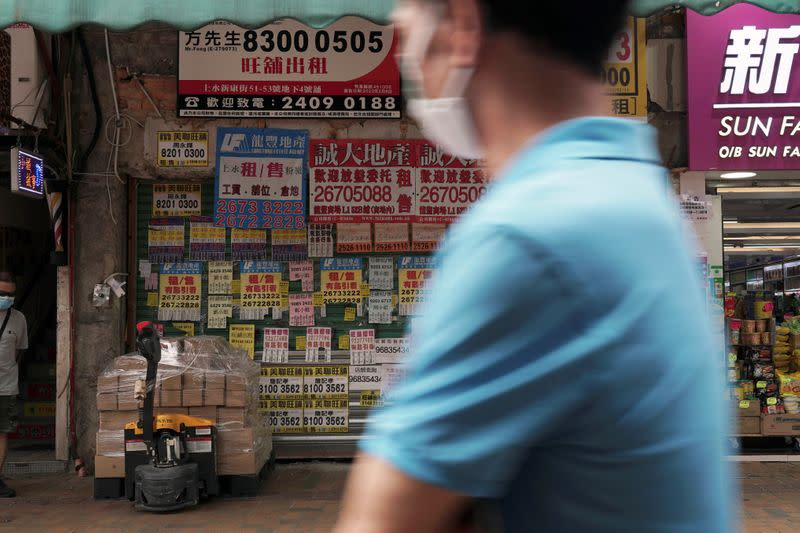 Man walks past a shuttered shop space covered in rental advertisements in Hong Kong's northern town of Sheung Shui