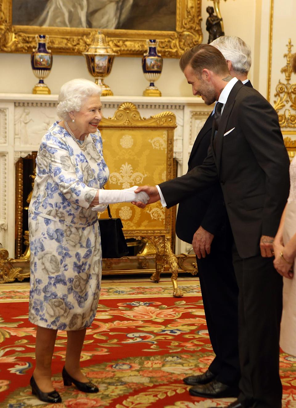 """<p>He may be one of the most famous people in the world but even David Beckham <a href=""""https://www.express.co.uk/celebrity-news/682898/David-Beckham-dapper-the-Queen-Buckingham-Palace-Young-Leaders-Awards"""" rel=""""nofollow noopener"""" target=""""_blank"""" data-ylk=""""slk:had"""" class=""""link rapid-noclick-resp"""">had</a> """"goosebumps"""" when he met the Queen. But he certainly dressed to impress in a dapper suit which, by the looks of Her Majesty's grin, she definitely approved of. <em>[Photo: Getty]</em> </p>"""