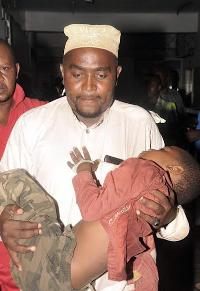 An injured child is carried to hospital in Mombasa Kenya, Saturday, May, 3, 2014. At least three have been confirmed dead and several others injured in twin explosions in the coastal city of Mombasa, Kenya, police said on Saturday. Mombasa Country police commander, Robert Kitur said they have not established the cause of the explosions at Reef Hotel Nyali and Mwembe Tayari in town. (AP Photo)