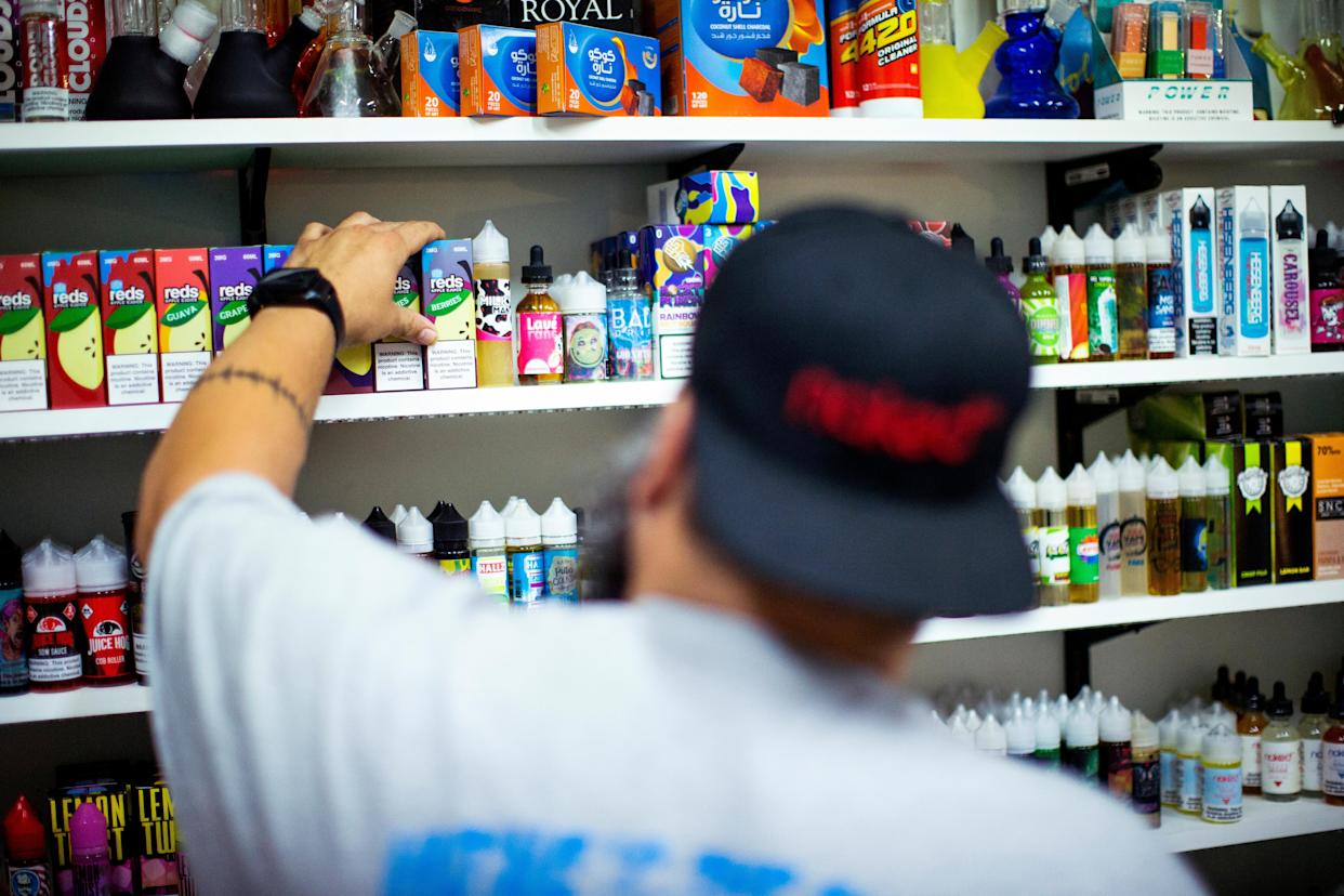 A vape shop worker organizes electronic smoking products in a local store in Jersey City, New Jersey, U.S., September 12, 2019. REUTERS/Eduardo Munoz