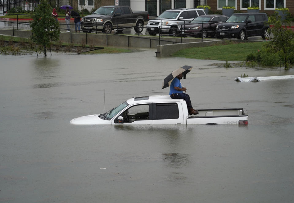 A man sits on top of a truck on a flooded road, Sept. 19, 2019, in Houston. Members of the Houston Fire Dept. brought him a life jacket and walked him to dry land. Throughout Texas and Louisiana, the remains of Tropical Depression Imelda kept bringing rains and flooding. (Photo: Melissa Phillip/Houston Chronicle via AP)