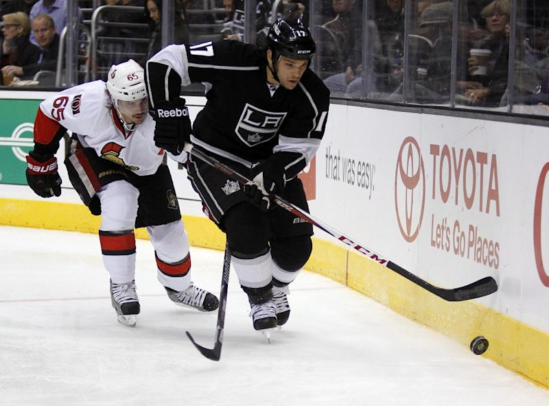 Los Angeles Kings left wing Daniel Carcillo (17) follows the puck with Ottawa Senators defenseman Erik Karlsson (65), of Sweden, defending during the second period of their NHL hockey game, Wednesday, Oct. 9, 2013, in Los Angeles. (AP Photo/Alex Gallardo)