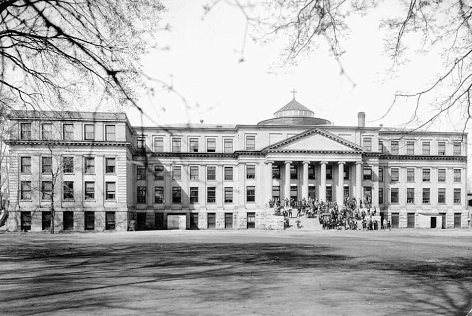 People standing on steps in front of a university building set back from a large grassy area in a black and white photo.