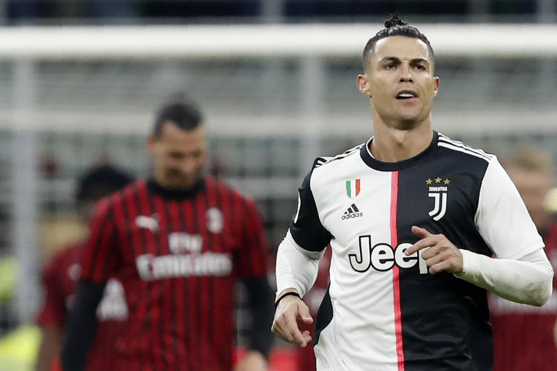 Juventus' Cristiano Ronaldo celebrates after scoring with penalty against AC Milan during an Italian Cup soccer match between AC Milan and Juventus at the San Siro stadium, in Milan, Italy, Thursday, Feb. 13, 2020. AC Milan's Zlatan Ibrahimovic is seen in the background. (AP Photo/Antonio Calanni)