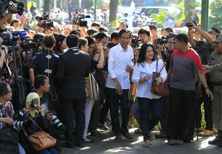 Jakarta governor and presidential candidate from the Indonesian Democratic Party-Struggle (PDI-P) party, Joko Widodo, and his wife Iriana (both in white) arrive to vote in the parliamentary elections, at a polling station in Jakarta April 9, 2014. REUTERS/Beawiharta