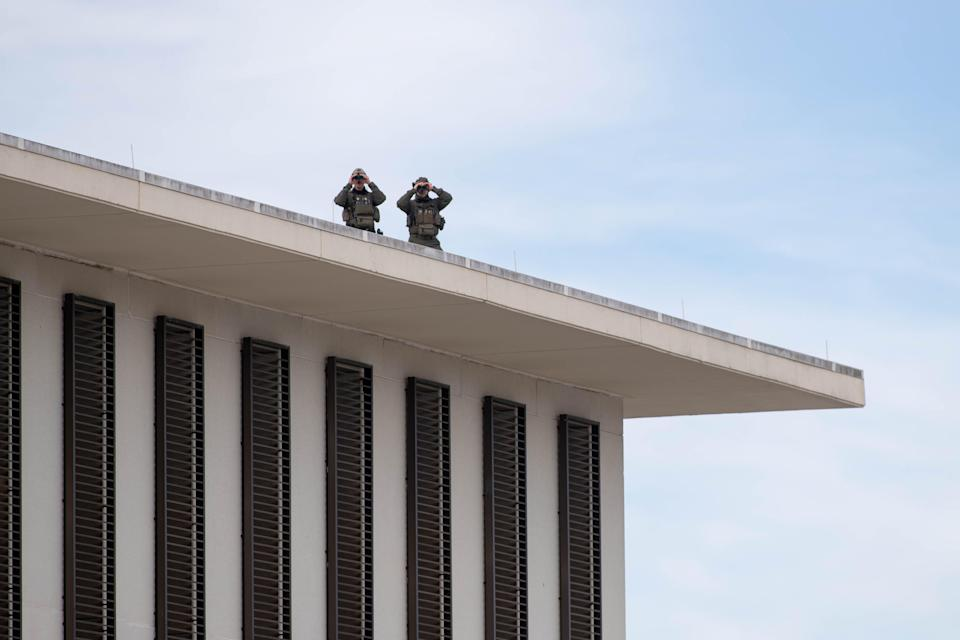 From atop the Florida House of Representatives Office Building in Tallahassee, members of law enforcement use binoculars to survey the area around the Florida Capitol Complex as multiple law enforcement agencies were stationed around the building as a precaution after FBI warnings of potential violence at state capitols on Sunday, Jan. 17, 2021.