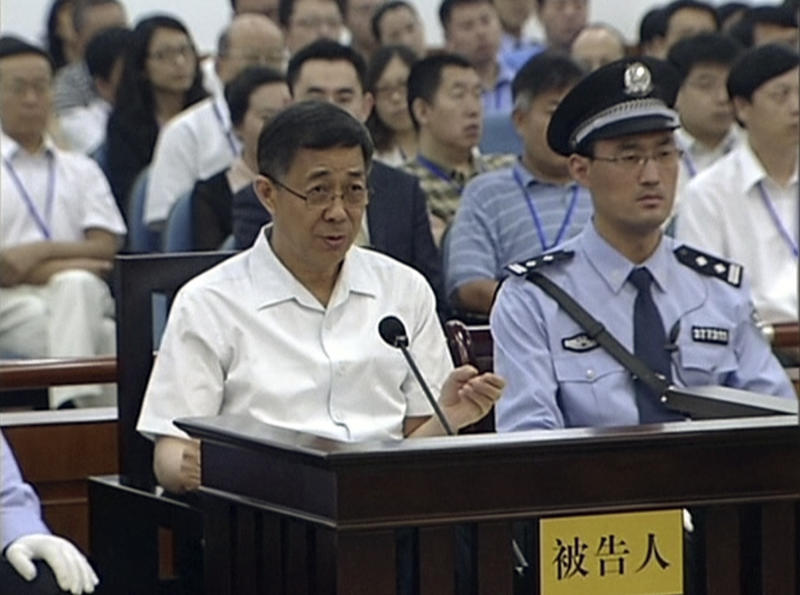 In this image taken from video, Former Chinese politician Bo Xilai, left, sits and speaks in a court room at Jinan Intermediate People's Court in eastern China's Shandong province, Friday, Aug. 23, 2013. Bo is accused of corruption and interference in the investigation of his wife's murder of a British businessman. (AP Photo/CCTV via AP Video) CHINA OUT, TV OUT