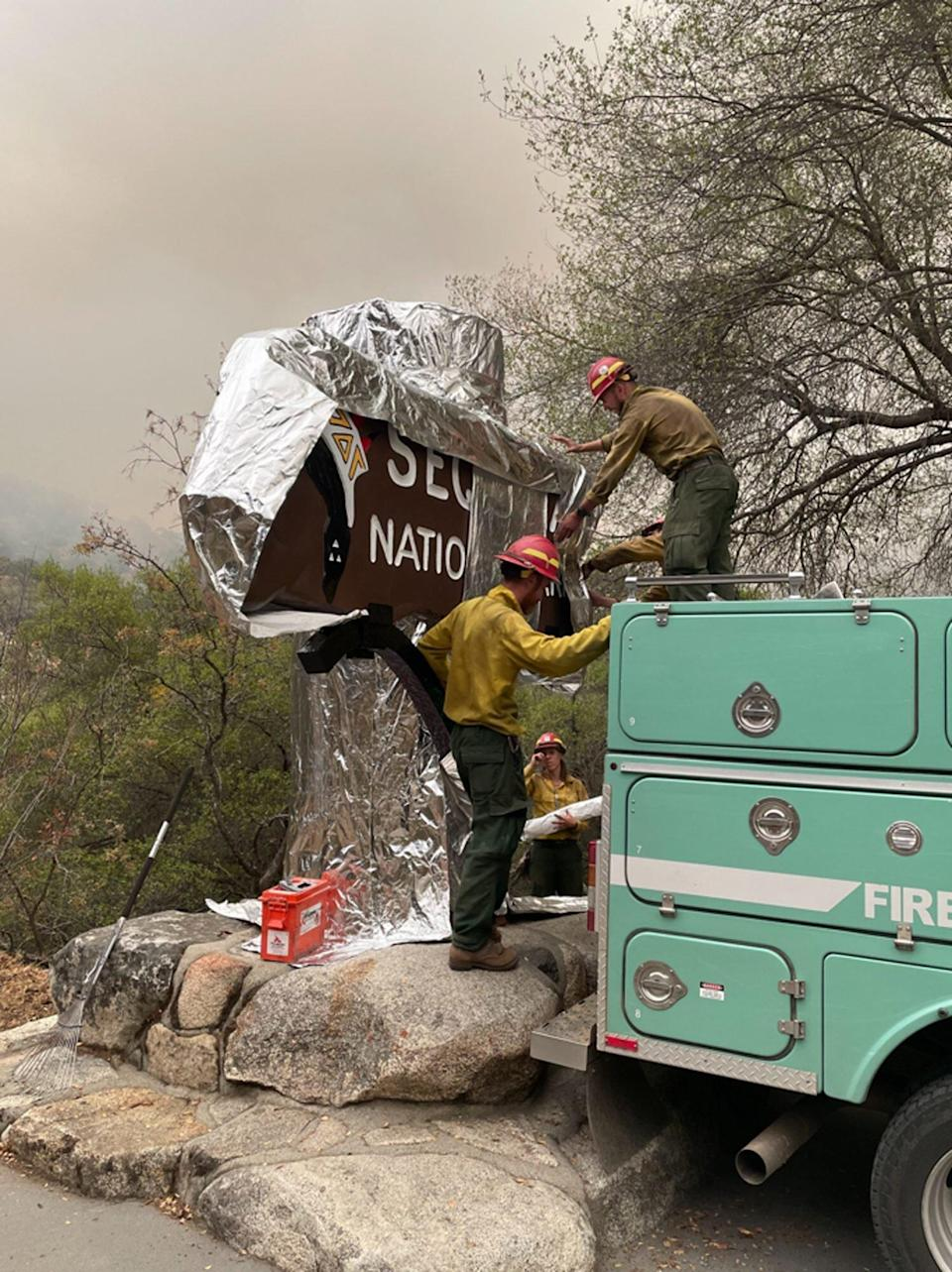 Firefighters put protective foil over historic Sequoia National Park Sign
