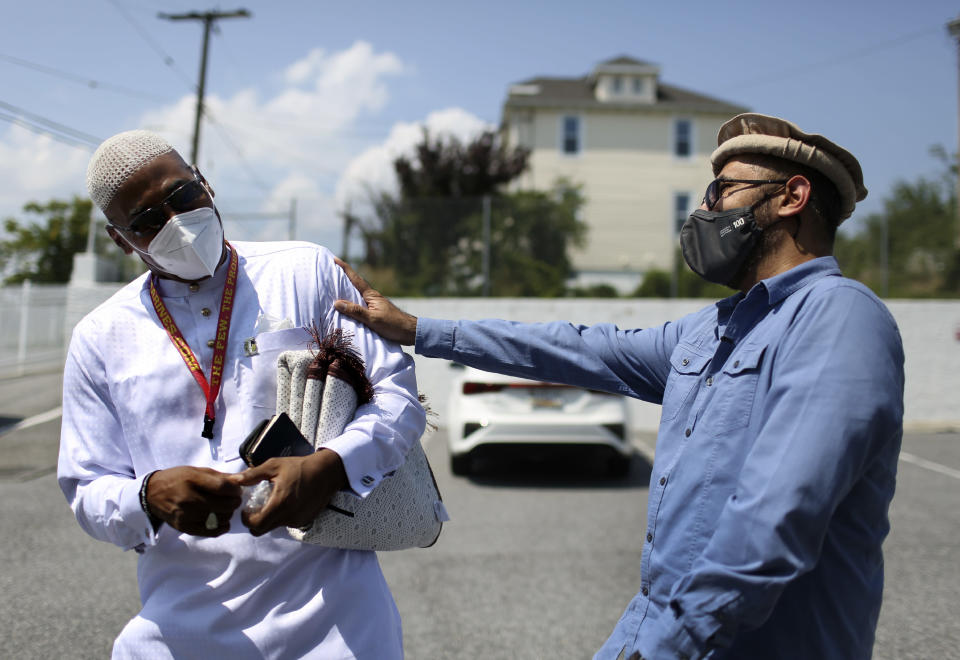 Abdul Latif Balanta, left, and Mansoor Shams joke with each other after Friday prayer in Rosedale, Md., on Friday, Aug. 13, 2021. In recent years, Shams has used his identity as both a Muslim and a former Marine to dispel misconceptions about Islam. (AP Photo/Jessie Wardarski)