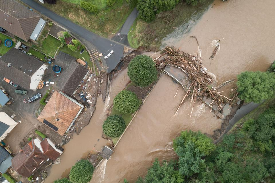 TOPSHOT - An aerial view taken on July 15, 2021 shows a bridge damaged by trunks following heavy rains and flood in Echtershausen, near Bitburg, western Germany. - Heavy rains and floods lashing western Europe have killed at least 59 people in Germany and eight in Belgium, and many more people are missing as rising waters caused several houses to collapse on July 15, 2021. (Photo by SEBASTIEN BOZON / AFP) (Photo by SEBASTIEN BOZON/AFP via Getty Images)