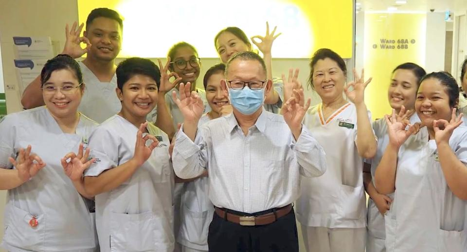 Mr Wang (centre with face mask), who was Singapore's first confirmed COVID-19 patient, poses with medical staff at Singapore General Hospital upon being discharged. (PHOTO: Screenshot/Lianhe Zaobao)