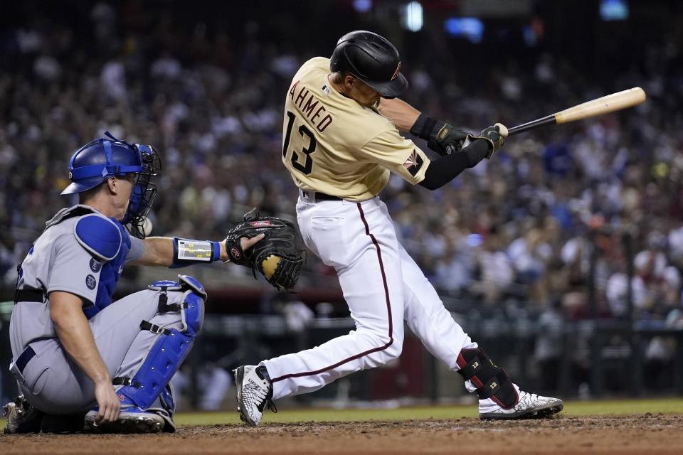 Arizona Diamondbacks' Nick Ahmed fouls a pitch off the face mask of Los Angeles Dodgers catcher Will Smith during the seventh inning of a baseball game Friday, June 18, 2021, in Phoenix. (AP Photo/Ross D. Franklin)