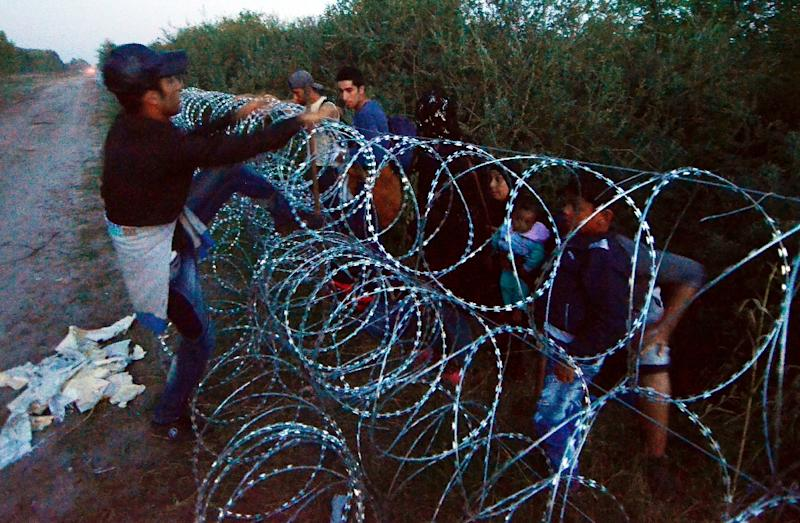 Migrants from several countries jump over a razor-wire fence at the Hungarian-Serbian border at Roszke village in Hungary, August 30, 2015 (AFP Photo/Csaba Segesvari)