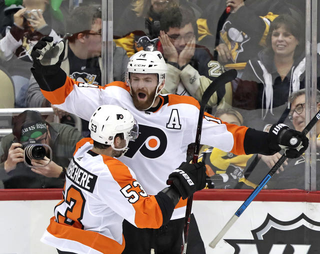 Philadelphia Flyers' Sean Couturier (14) celebrates with Shayne Gostisbehere (53) after getting the game-winning goal past Pittsburgh Penguins goaltender Matt Murray in the overtime of an NHL hockey game in Pittsburgh, Sunday, March 17, 2019. The Flyers won 2-1. (AP Photo/Gene J. Puskar)