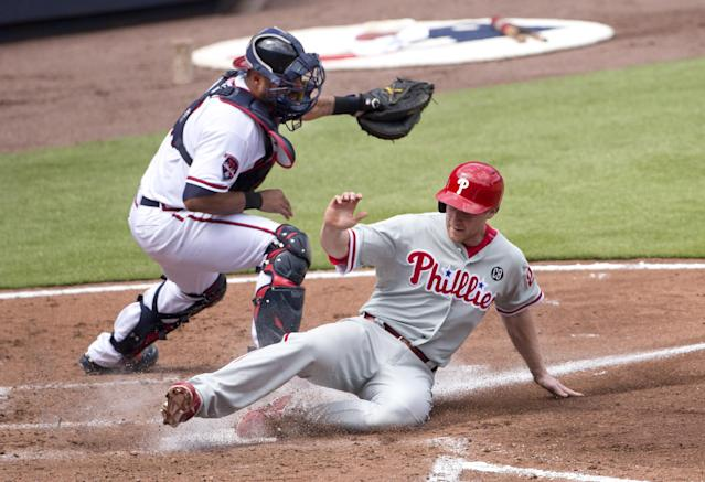 Philadelphia Phillies' Cody Asche (25) scores on a Ben Revere sacrifice fly as Atlanta Braves catcher Gerald Laird (11) handles the late throw in the third inning of a baseball game Monday, Sept. 1, 2014, in Atlanta. (AP Photo/John Bazemore)