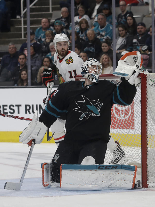 San Jose Sharks goaltender Martin Jones reaches for the puck during the second period of the team's NHL hockey game against the Chicago Blackhawks in San Jose, Calif., Thursday, March 28, 2019. (AP Photo/Jeff Chiu)
