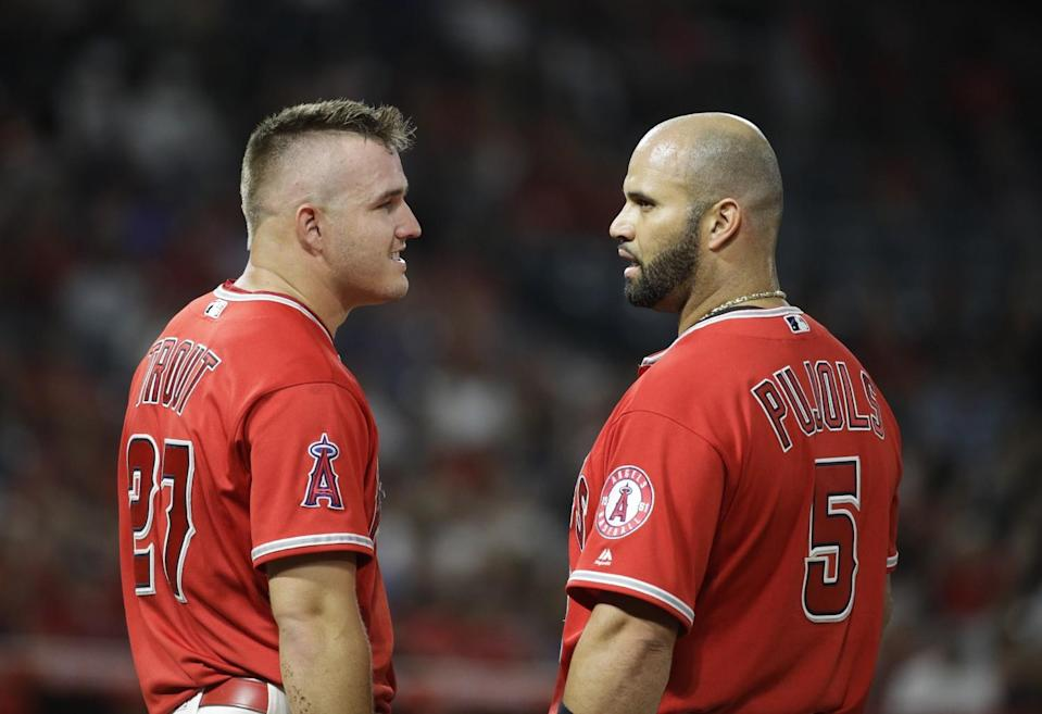 The Angels' Mike Trout, left, chats with Albert Pujols during a game Aug. 30, 2017.