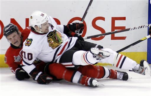 Ottawa Senators' Chris Neil, left, reacts after colliding with Chicago Blackhawks' Patrick Sharp during first-period NHL hockey game action in Ottawa, Ontario, Friday, March 2, 2012. (AP Photo/The Canadian Press, Fred Chartrand)