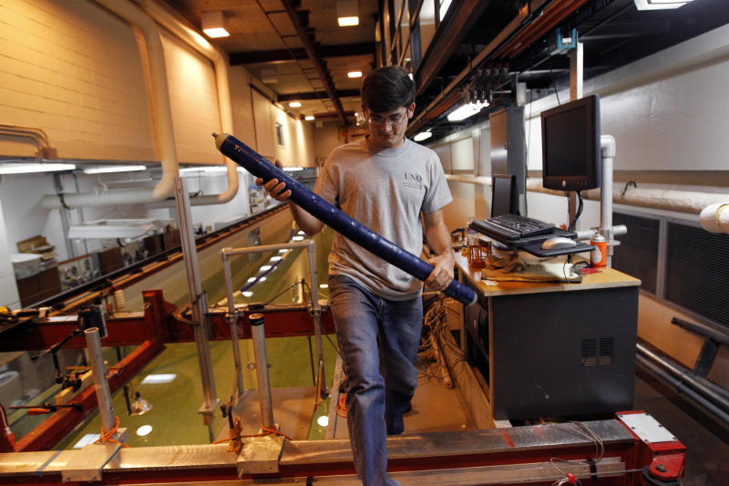 Graduate student Baker Potts handles a prototype robotic eel inside the engineering building at the University of New Orleans Tuesday, Oct. 2, 2012 in New Orleans. The robotic eel might be able to wriggle through dangerous waters with almost no wake, letting it move on little power and with little chance of radar detection as it looks for underwater mines. (AP Photo/Gerald Herbert)