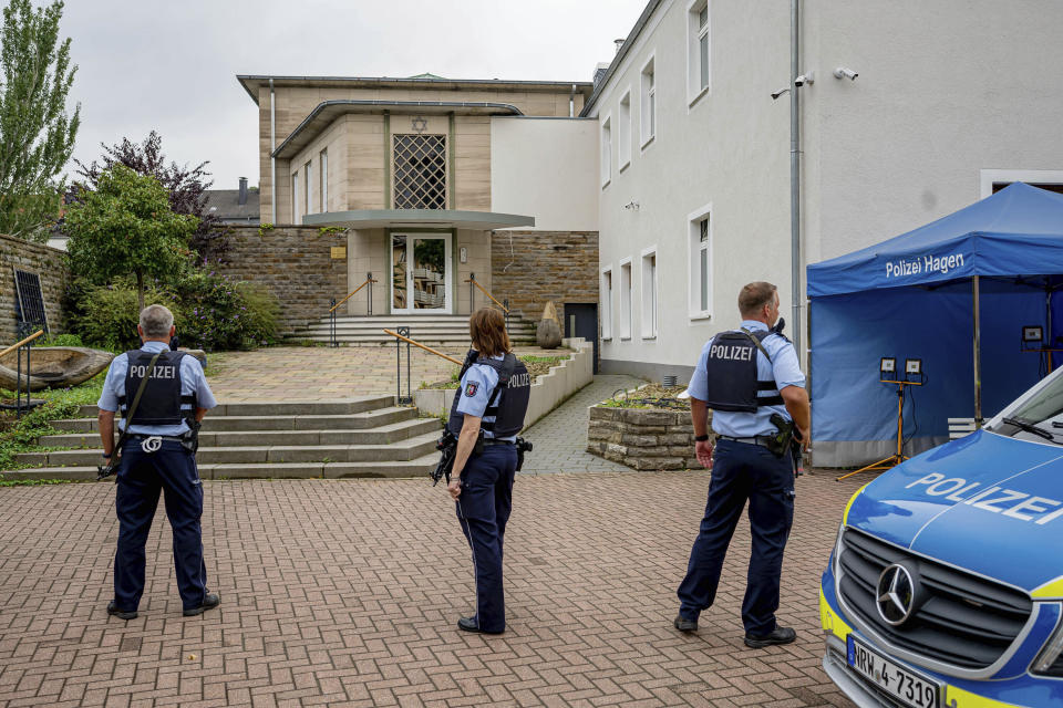 Police officers stay in front of the entrance to the Jewish Community building in Hagen, Germany, Tursday, Sept. 16, 2021. Numerous police officers protected the synagogue in the night, the police spoke of indications of a possible dangerous situation. (Henning Kaiser/dpa via AP)