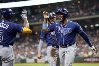 Tampa Bay Rays' Yandy Diaz, right, celebrates with Wander Franco, left, after hitting a two-run home run against the Houston Astros during the first inning of a baseball game Tuesday, Sept. 28, 2021, in Houston. Tampa Bay Rays' Brandon Lowe, rear, scored on Diaz's homer. (AP Photo/David J. Phillip)