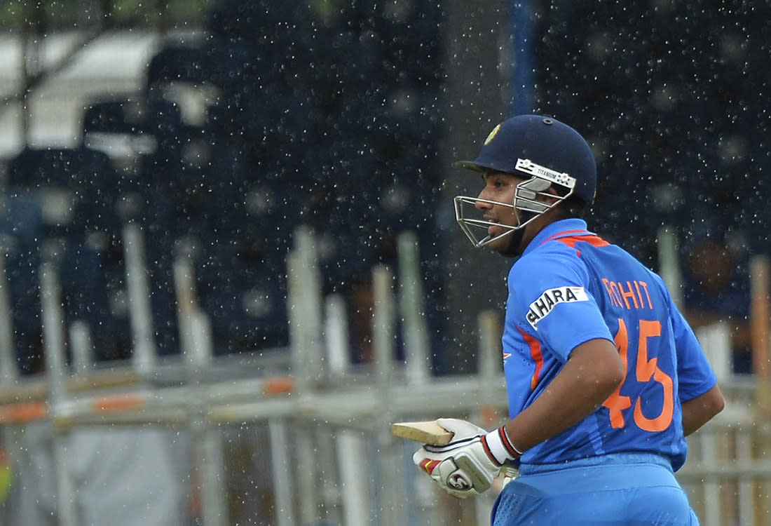 Indian cricketer Rohit Sharma runs to the dress room as rain interrupts the sixth match of the Tri-Nation series between India and Sri Lanka at the Queen's Park Oval stadium in Port of Spain on July 9, 2013. Sri Lanka won the toss and elected to field first. AFP PHOTO/Jewel Samad
