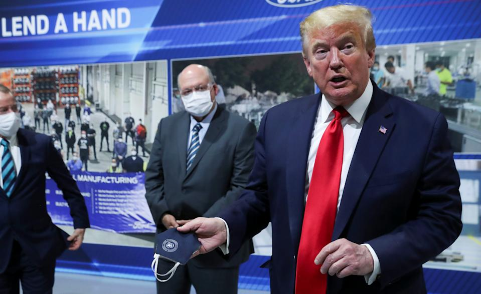 U.S. President Donald Trump holds a protective face mask with a presidential seal on it that he said he had been wearing earlier in his tour as Ford Motor Company CEO Jim Hackett looks on. REUTERS/Leah Millis