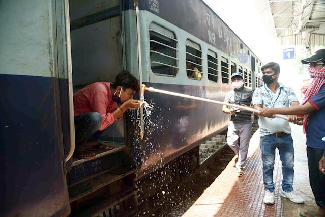 A railway employee helps a migrant on a Shramik Special train to drink water in Patna, India. (Photo by Santosh Kumar/Hindustan Times via Getty Images)