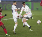 Real Madrid's Karim Benzema, center left, and Real Madrid's Marco Asensio both jump for a shot during the Spanish La Liga soccer match between Real Madrid and Granada at the Alfredo Di Stefano stadium in Madrid, Spain, Wednesday, Dec. 23, 2020. (AP Photo/Bernat Armangue)