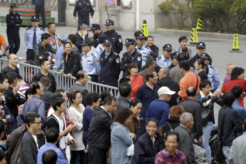 Chinese police officers monitor residents gathered outside the city government office in Ningbo city in eastern China's Zhejiang province Monday, Oct. 29, 2012. After three days of protests by thousands of citizens over pollution fears, a local Chinese government relented and agreed that the petrochemical factory would not be expanded, only to see the protests persist. (AP Photo/Ng Han Guan)